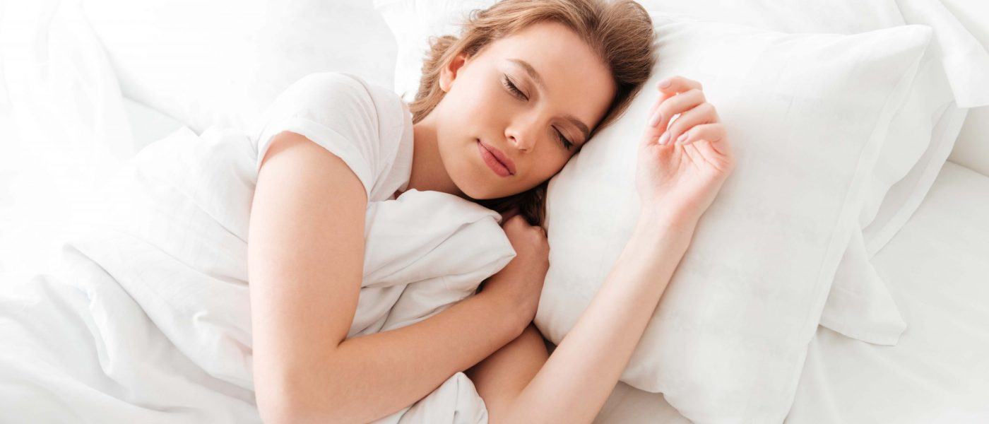 Photo of sleeping young woman lies in bed with eyes closed.